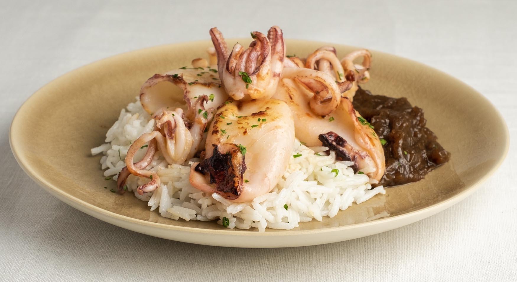 Calamares frescos encebollados sobre cama de cebolla caída y arroz basmati