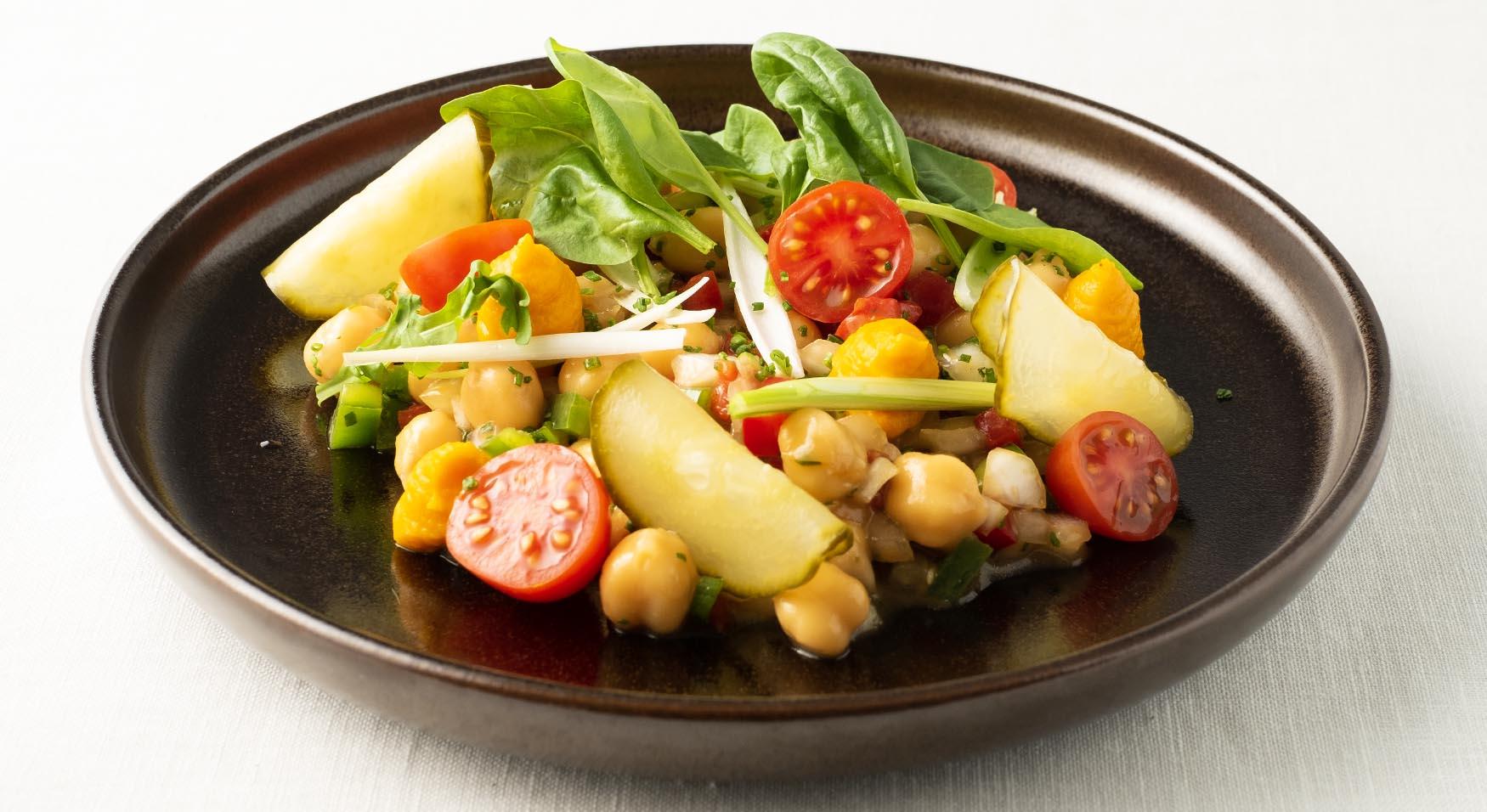 Ensalada de garbanzo con hojas frescas, encurtidos y verduras
